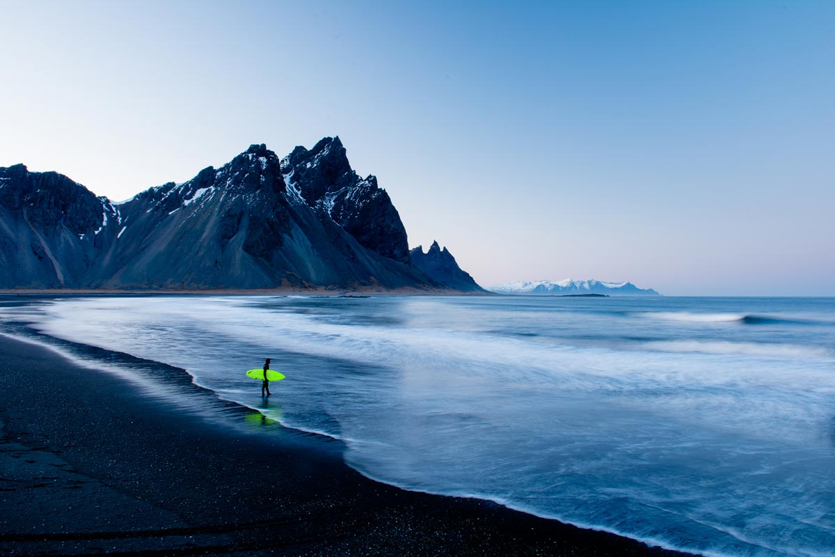 Chris Burkard photo of man with surfboard walking into frigid waters