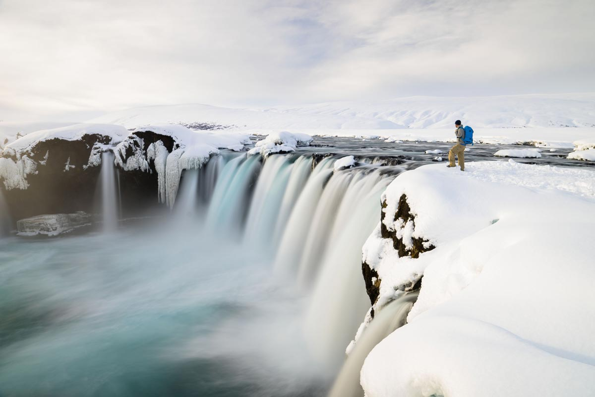 Chris Burkard photo of man looking down at arctic waterfall