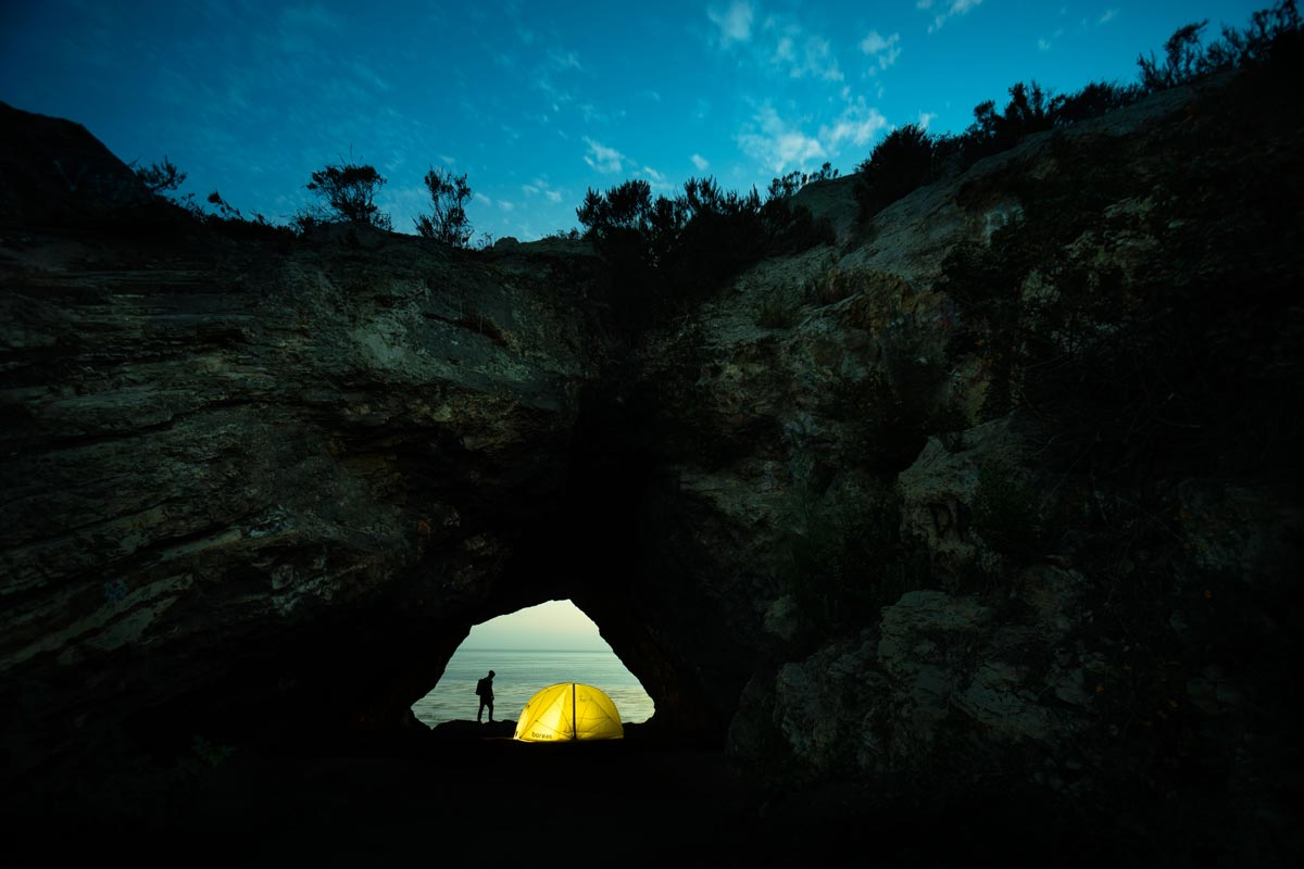 Chris Burkard photo of illuminated tent in center of coastal archway at nightfall