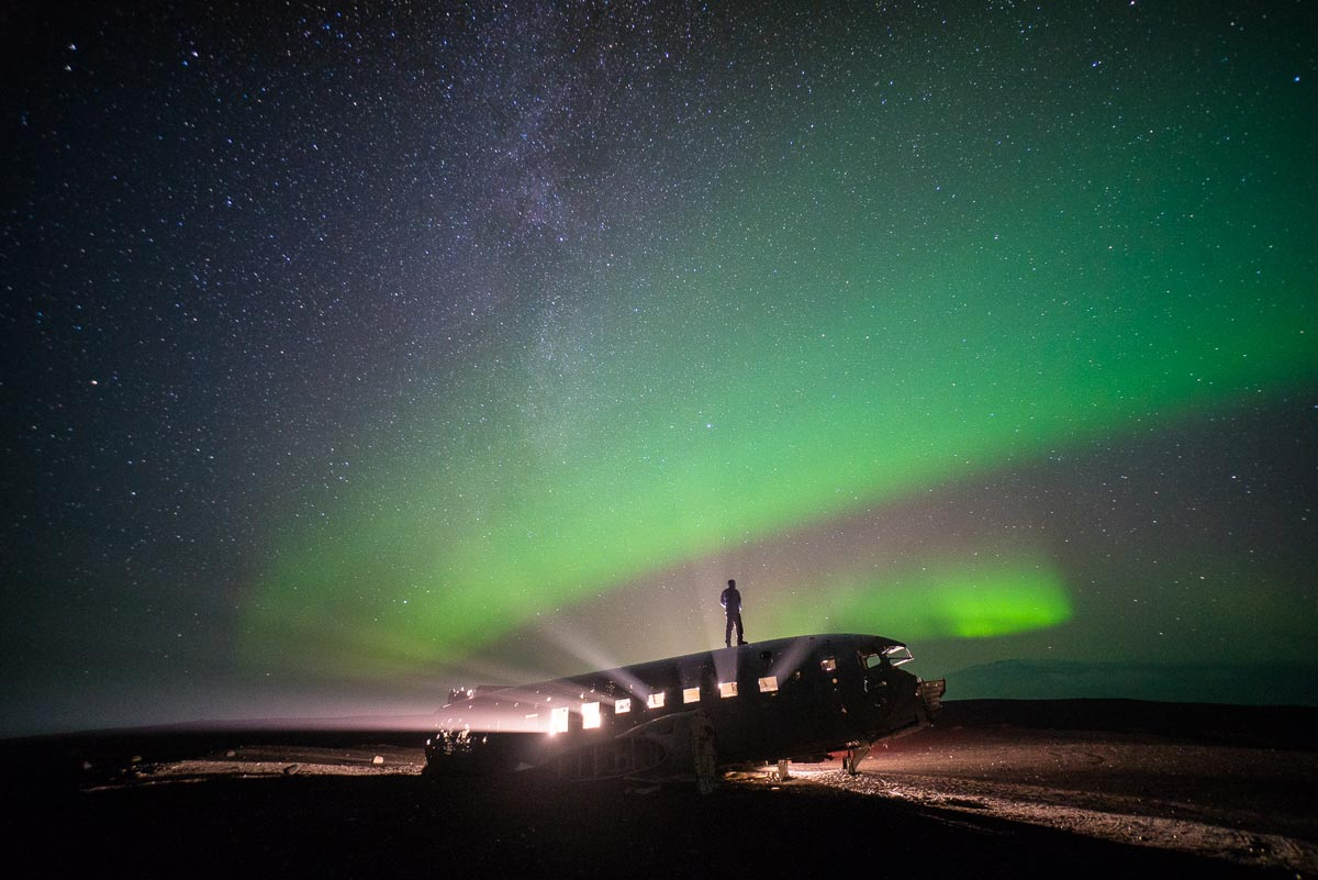Chris Burkard photo of man standing atop a small plane in front of the Aurora Borealis