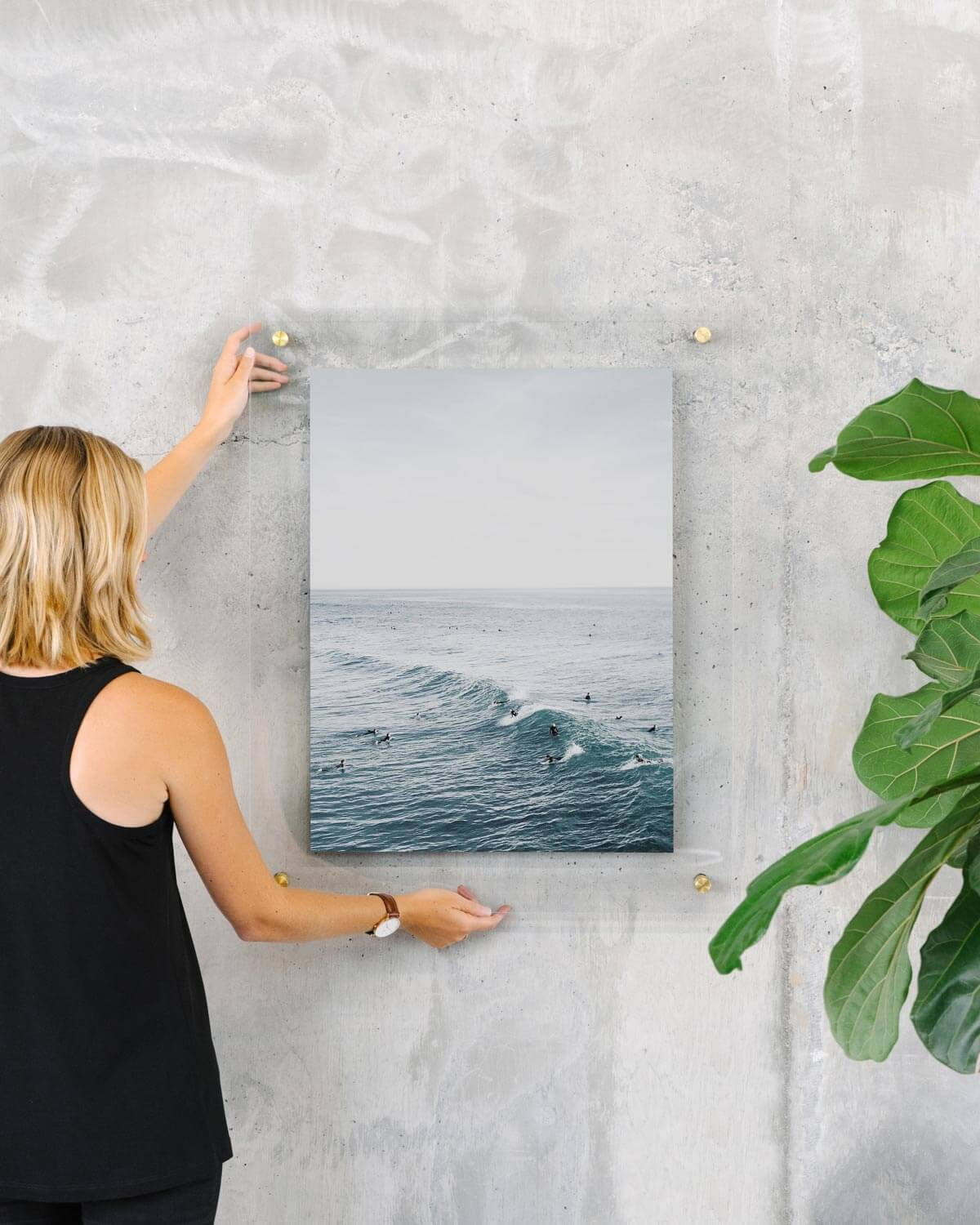 Woman hanging floating frame with photo of ocean