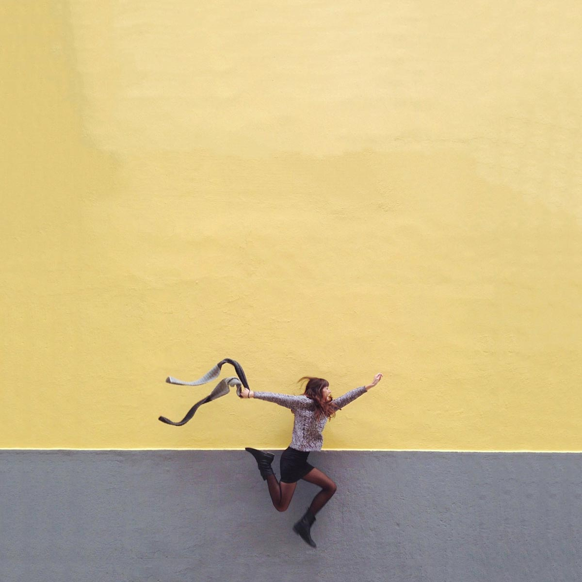 Photo by Daniel Rueda of woman jumping in front of yellow and gray backdrop