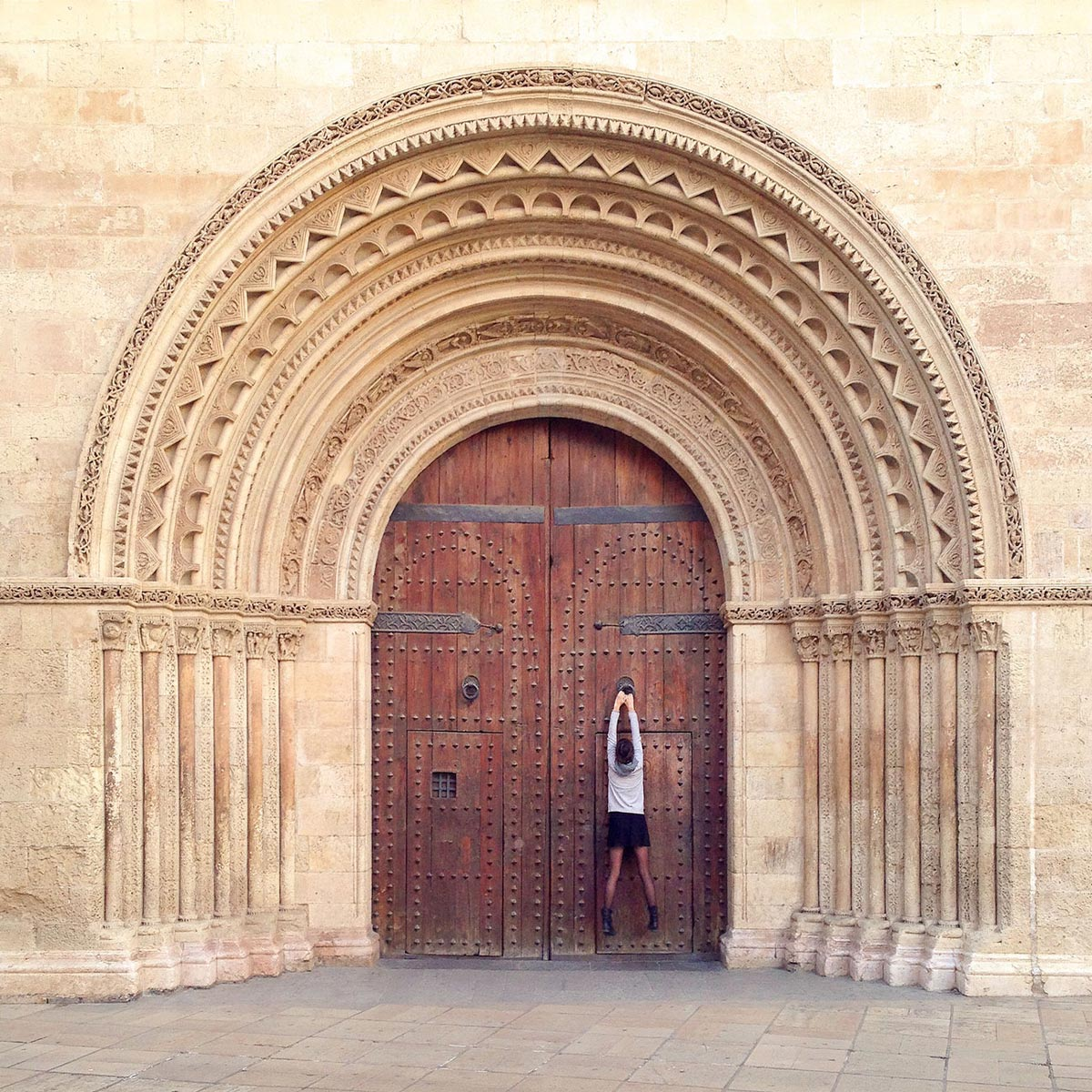 Photo by Daniel Rueda of woman holding onto doorstop of a gigantic wooden door