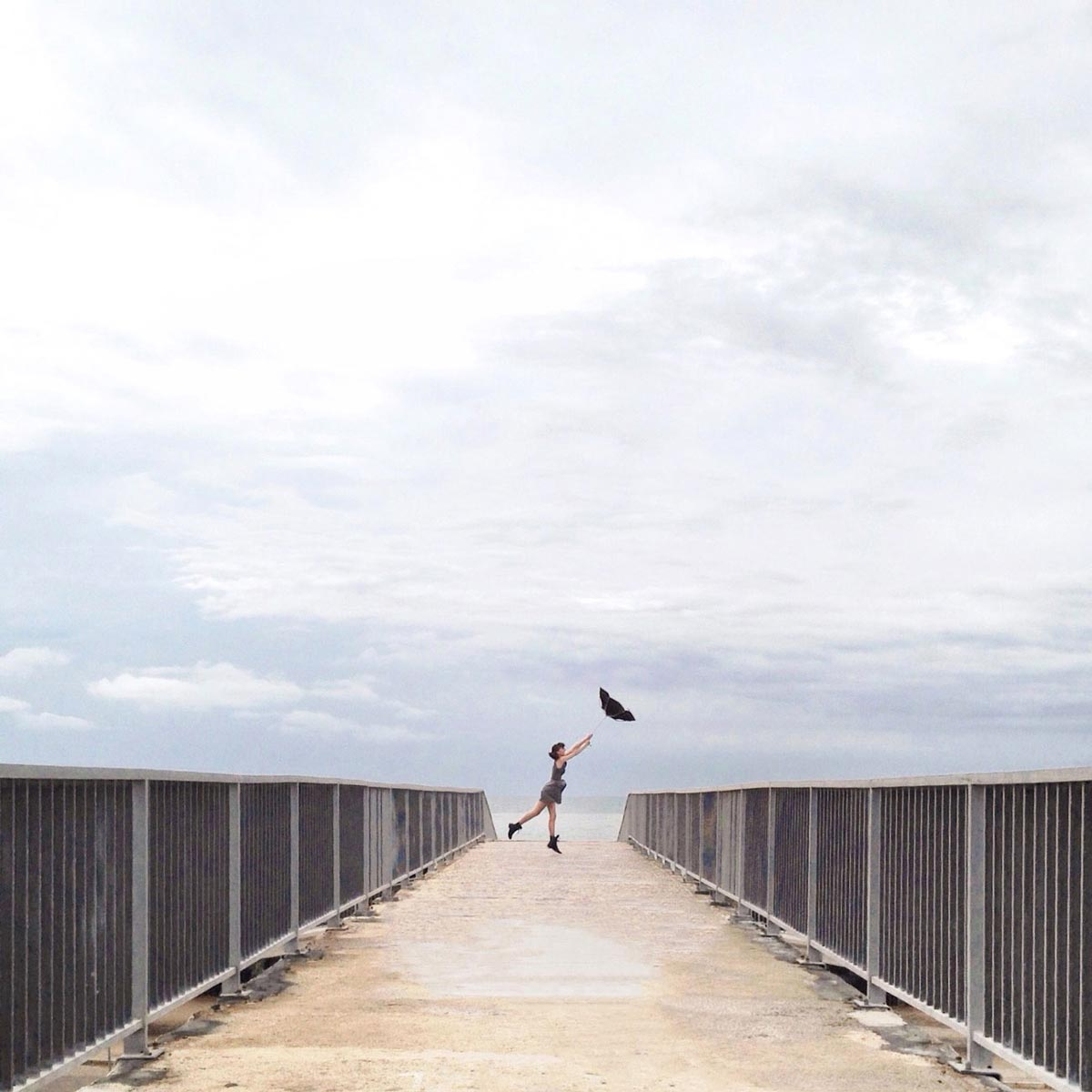Photo by Daniel Rueda of woman holding onto inverted umbrella at the end of a pier