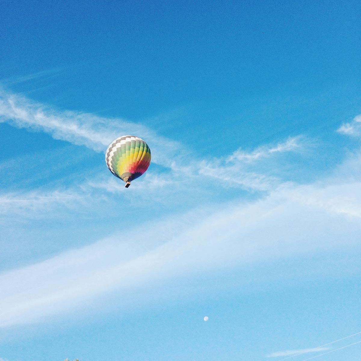 Photo by Max Wanger of hot air baloon flying into vivid blue sky