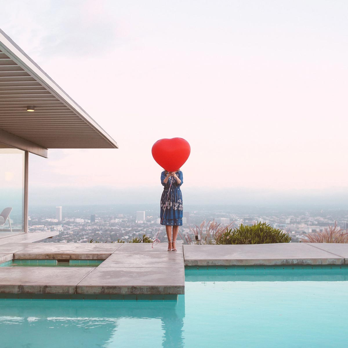 Photo by Max Wanger of woman holding giant heart baloon in front of her face