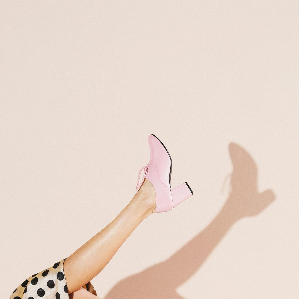 Photo by Max Wanger of leg in pink heeled shoe kicking up