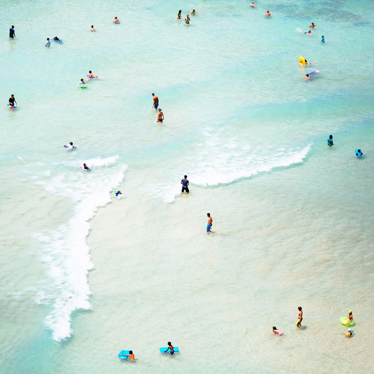 Photo by Max Wanger of people frolicking in the cool blue ocean water