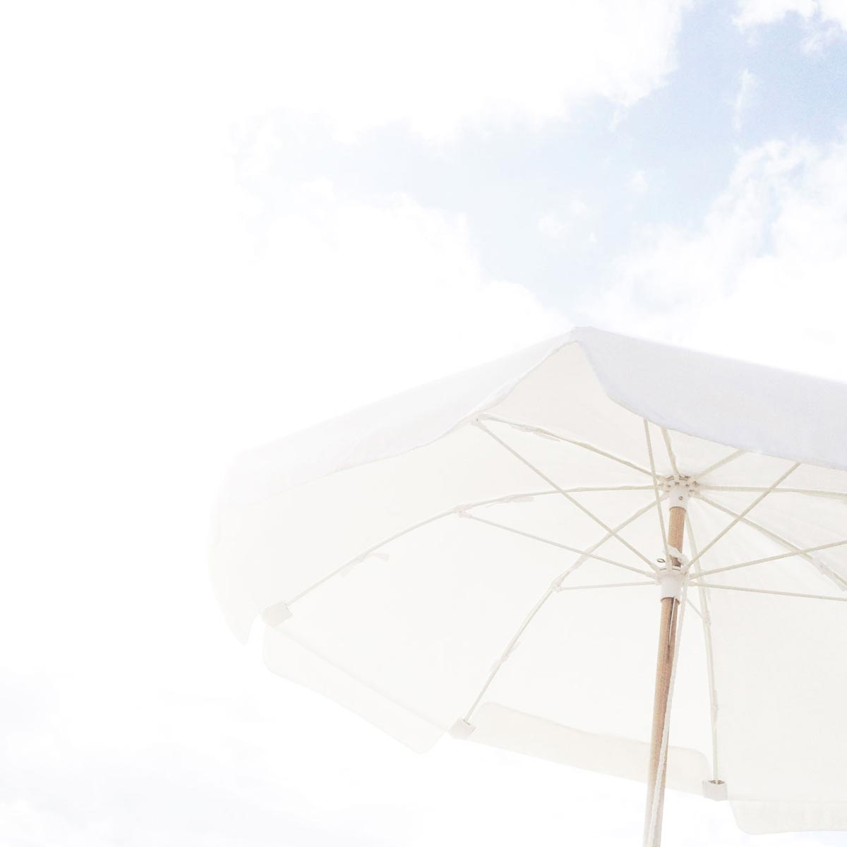 Photo by Stefanie Etow of large white beach umbrella in the corner of a photo of the sky