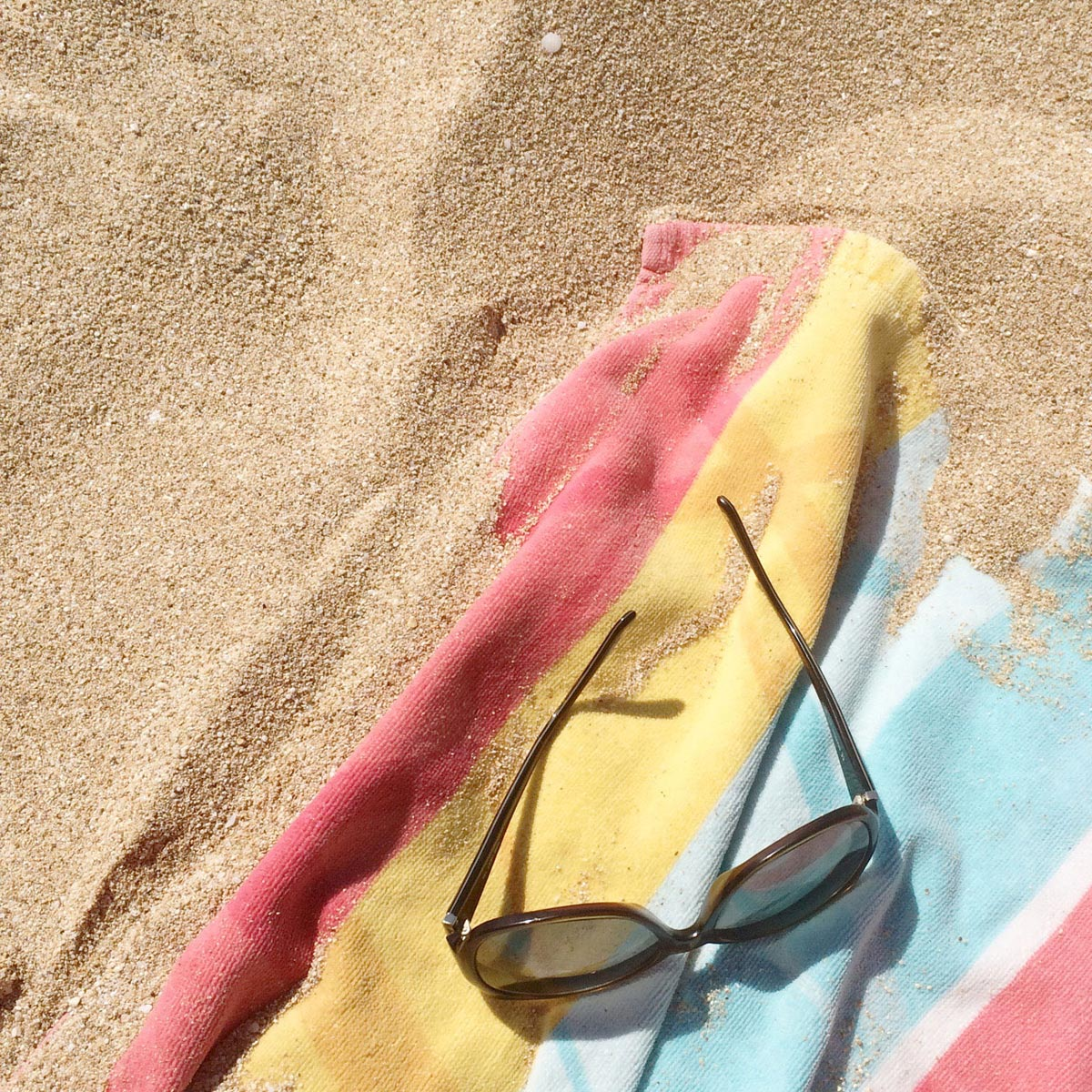 Photo by Stefanie Etow of beach towel and sunglasses at the bottom right corner of image