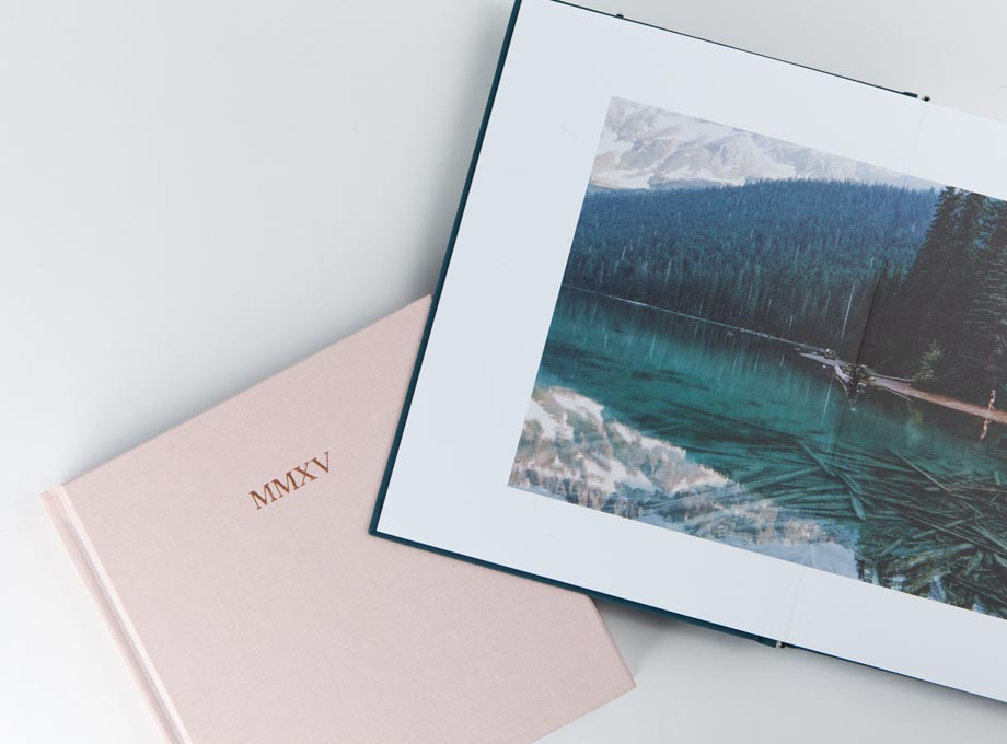 Photo book opened to two-page photo of alpine lake