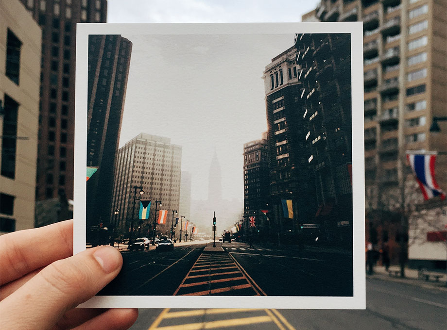 Hand holding up photo of city street