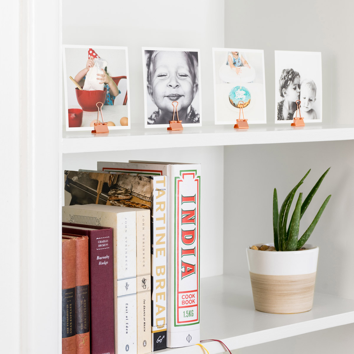 Photo prints on mantel held by binder clips