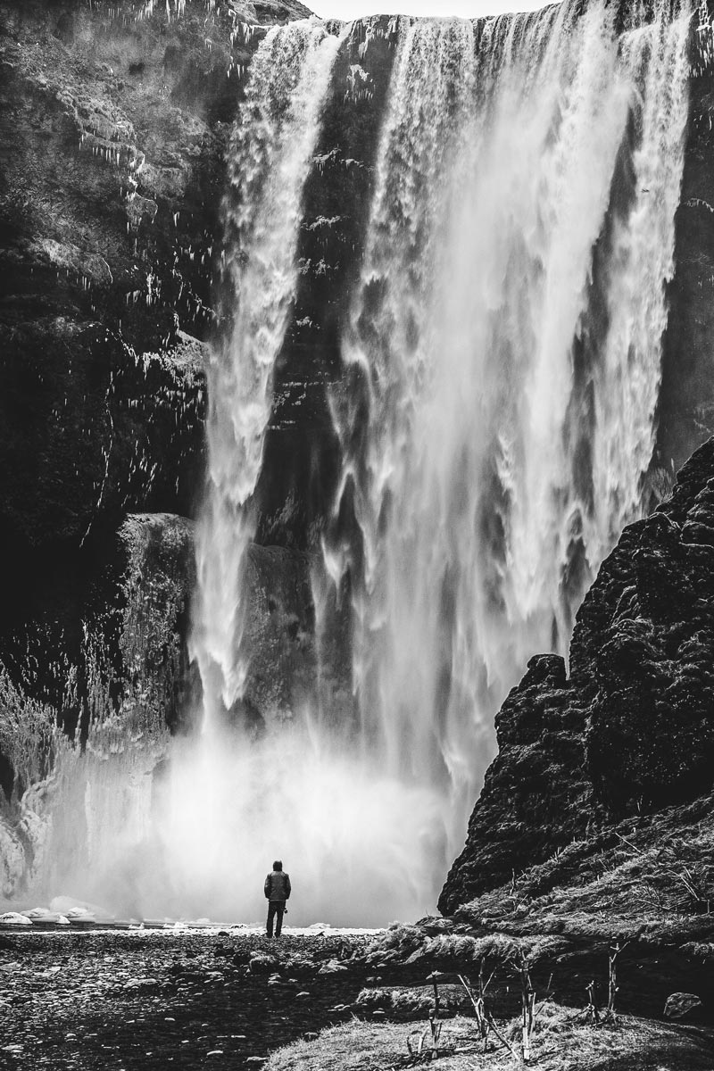 Black and white photo by Jason Peterson of person in front of waterfall