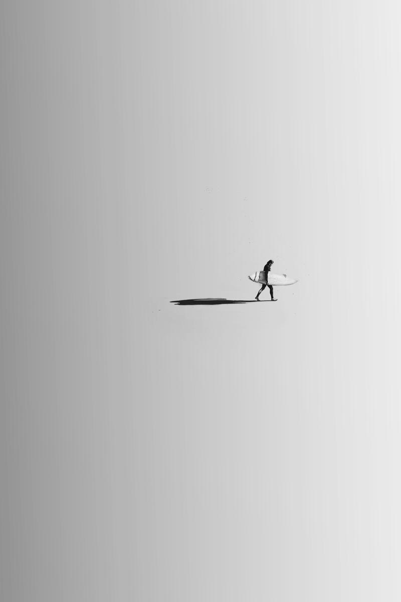 Black and white photo by Jason Peterson of person walking with their surfboard