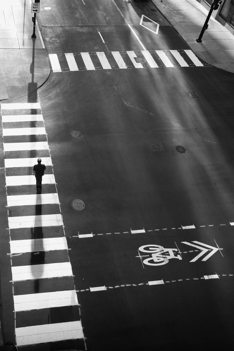 Black and white photo of Jason Peterson walking across crosswalk at traffic light