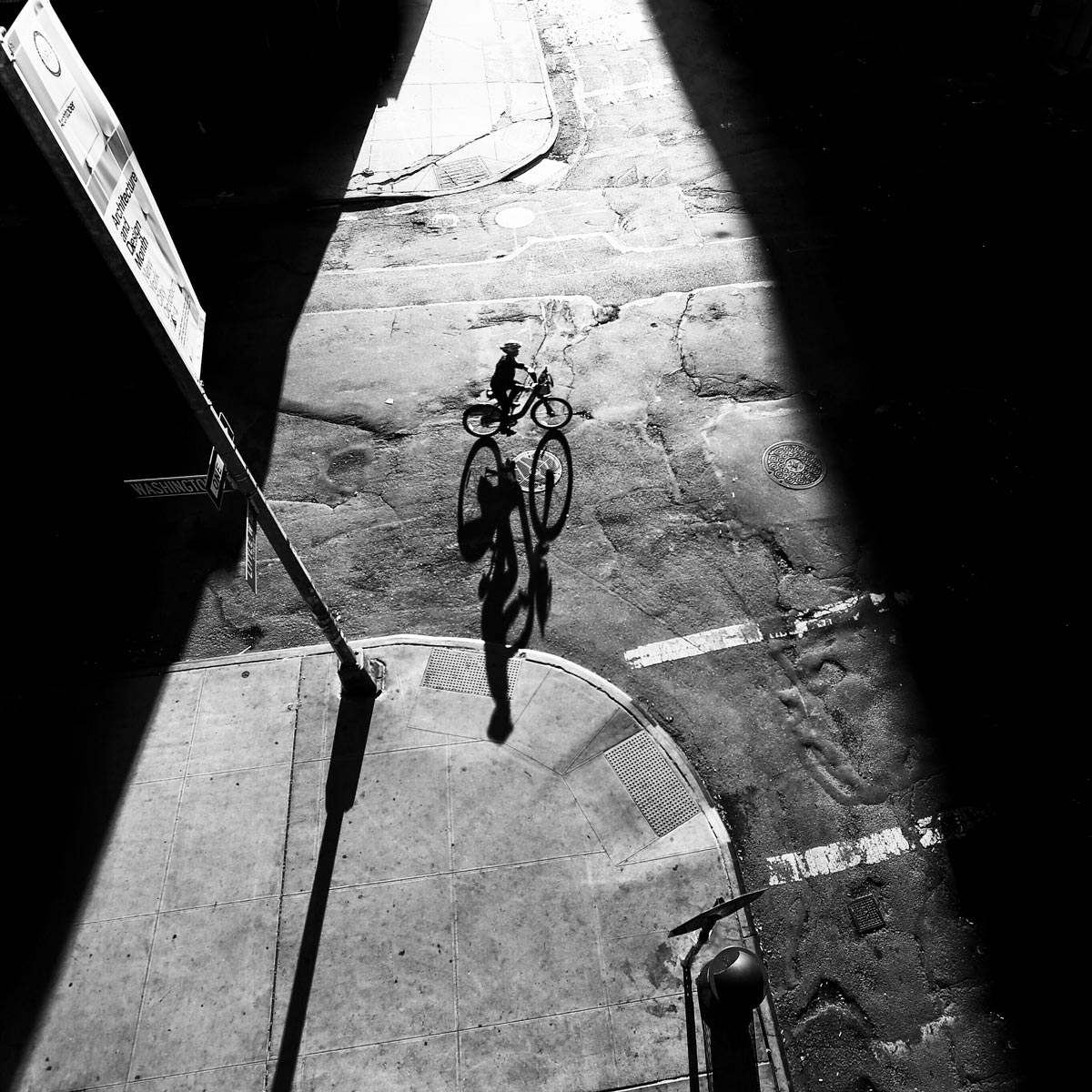 Black and white photo by Jason Peterson of someone biking through sliver of light