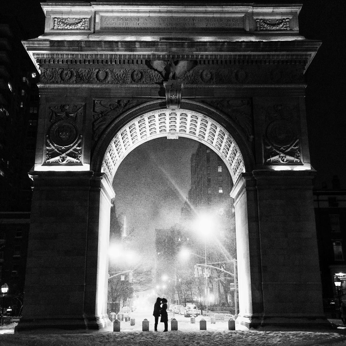 Black and white photo by Jason Peterson of couple kissing under arc de triomphe at night