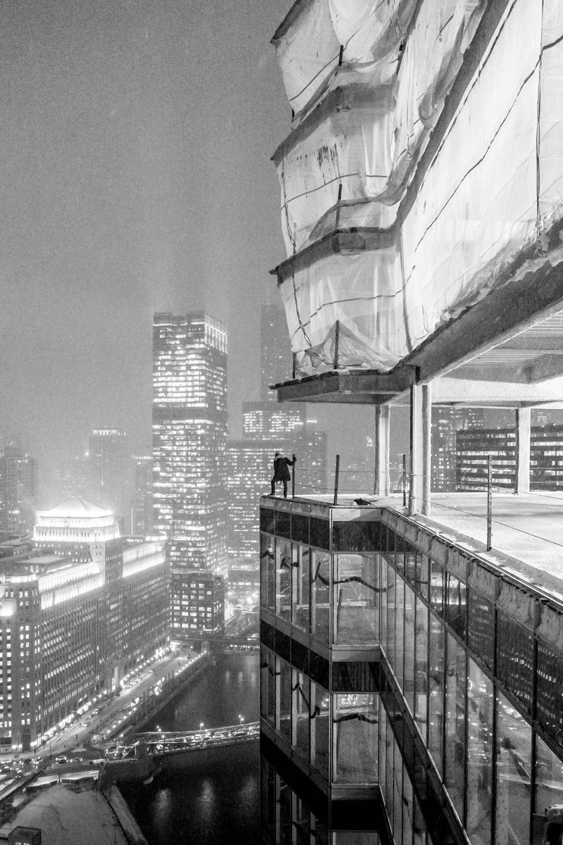 Photo of person standing at the edge of a skyscraper under construction by Jason Peterson