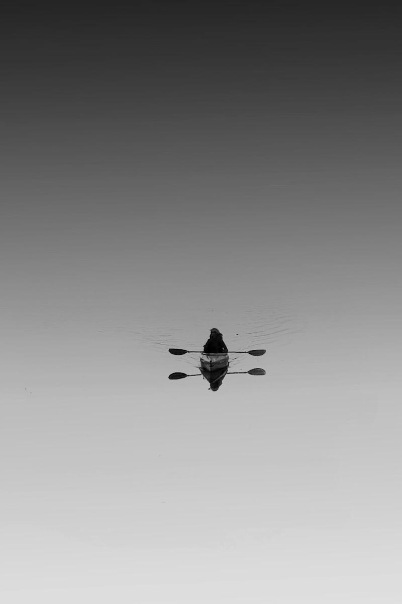 Black and white photo of someone canoeing on still waters by Jason Peterson