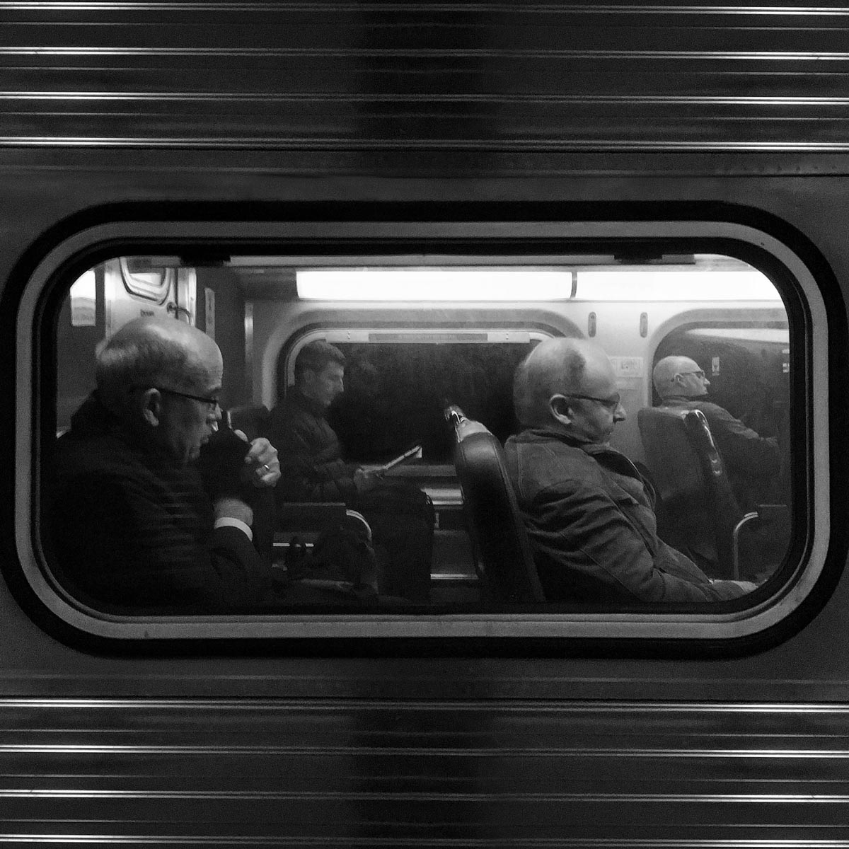 Black and white photo of old men through train window by Jason Peterson