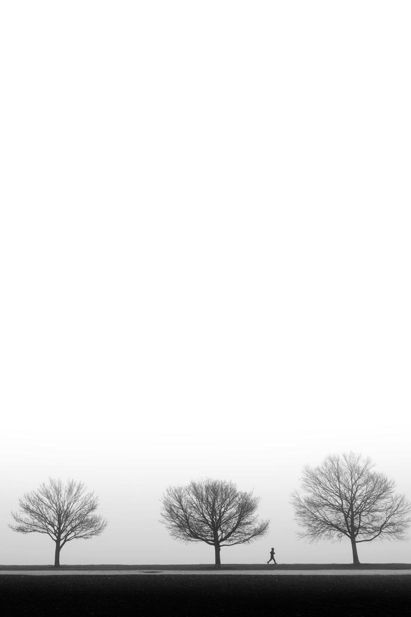 Black and white photo of someone running in front of trees by Jason Peterson