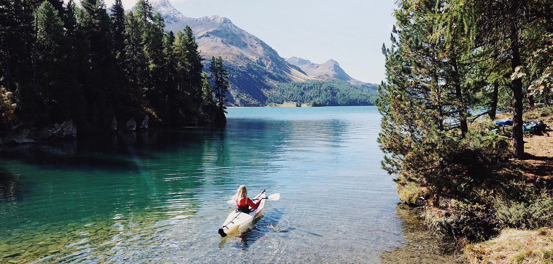 Woman kayaking in beautiful alpine lake