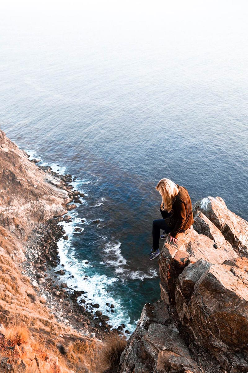 Photo by Christian Schaffer of girl sitting at the edge of a rock on coastal cliffs