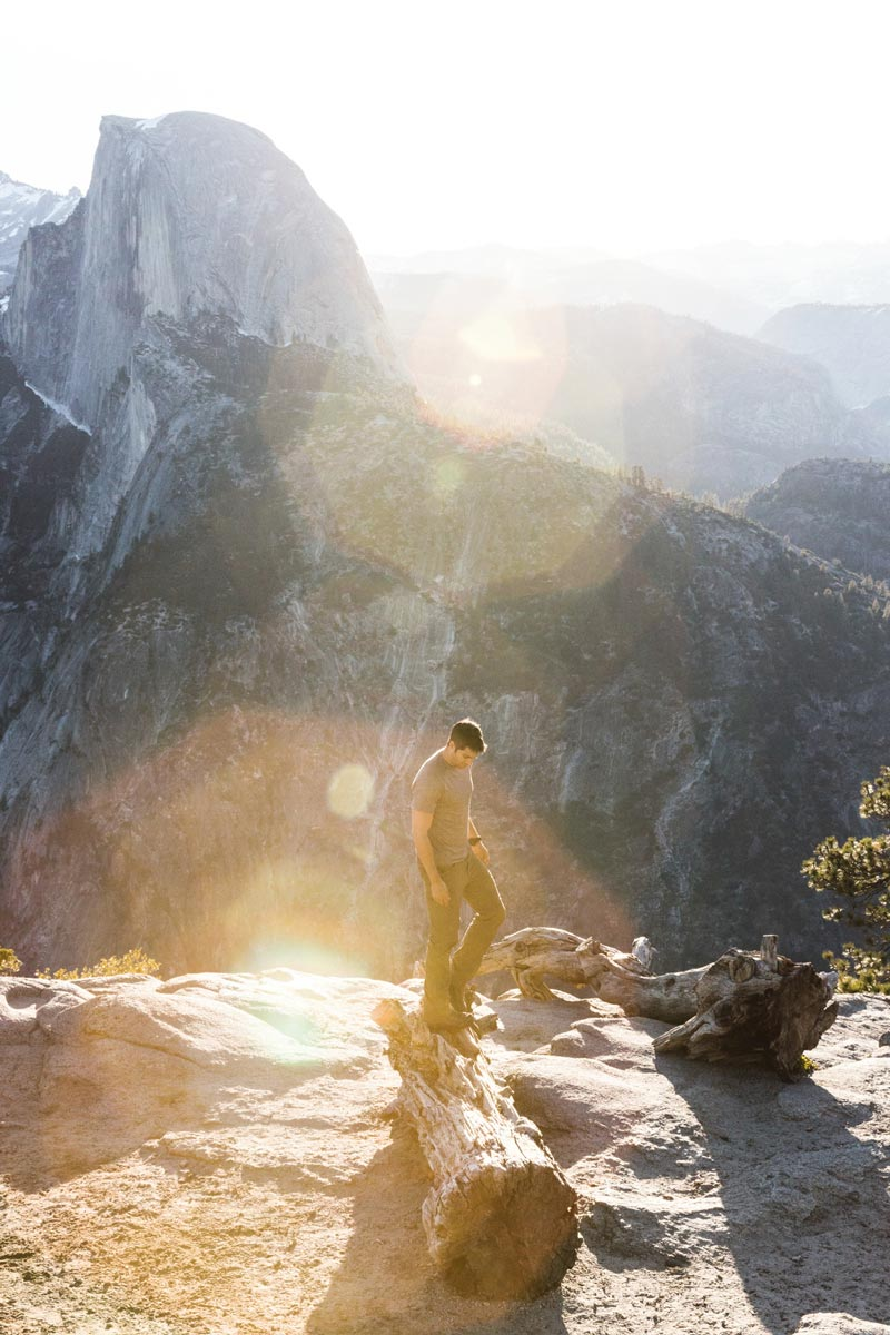 Photo by Christian Schaffer of man standing on log across from El Capitan