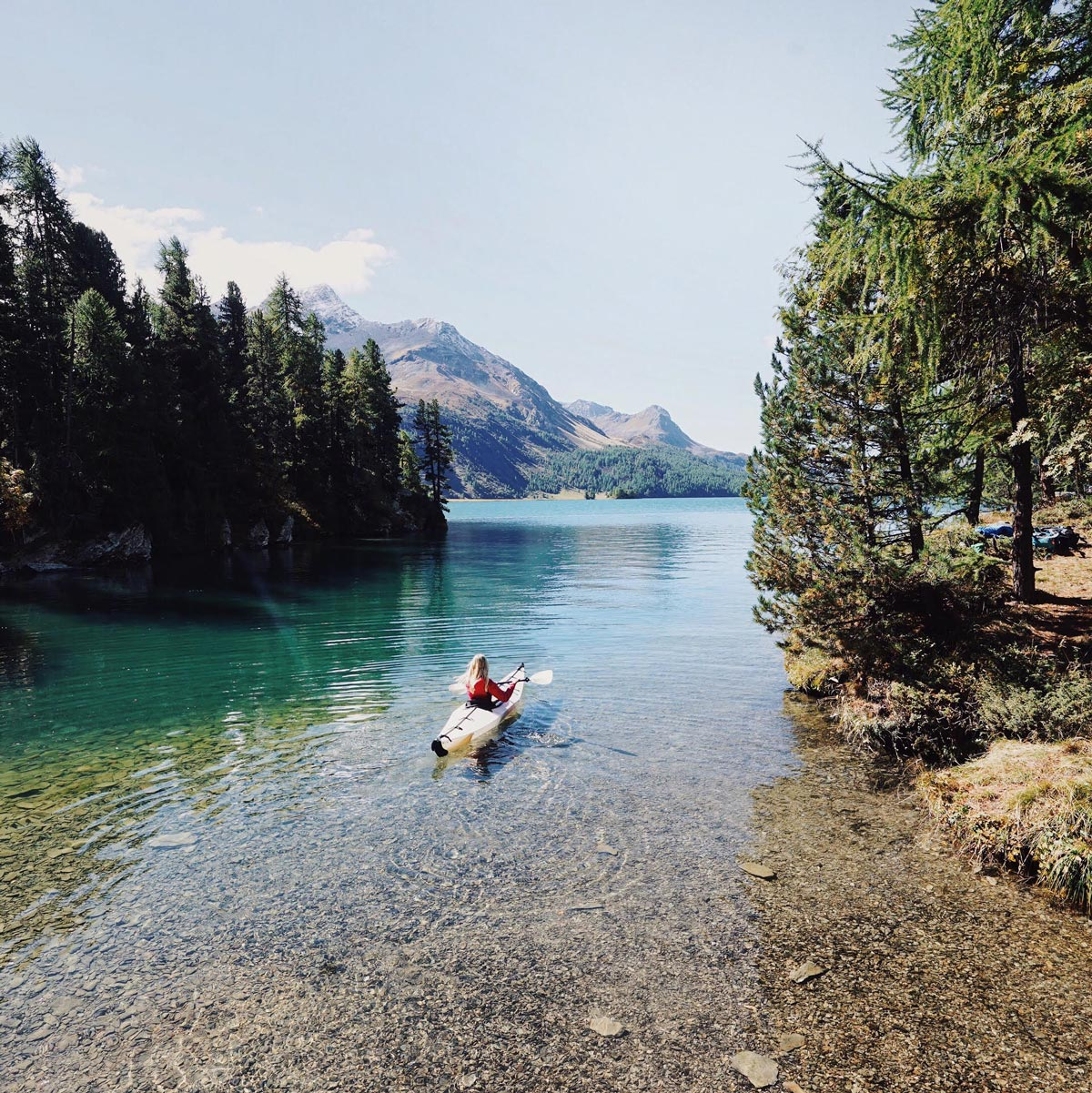 Photo by Martina Bisaz of woman kayaking in alpine lake