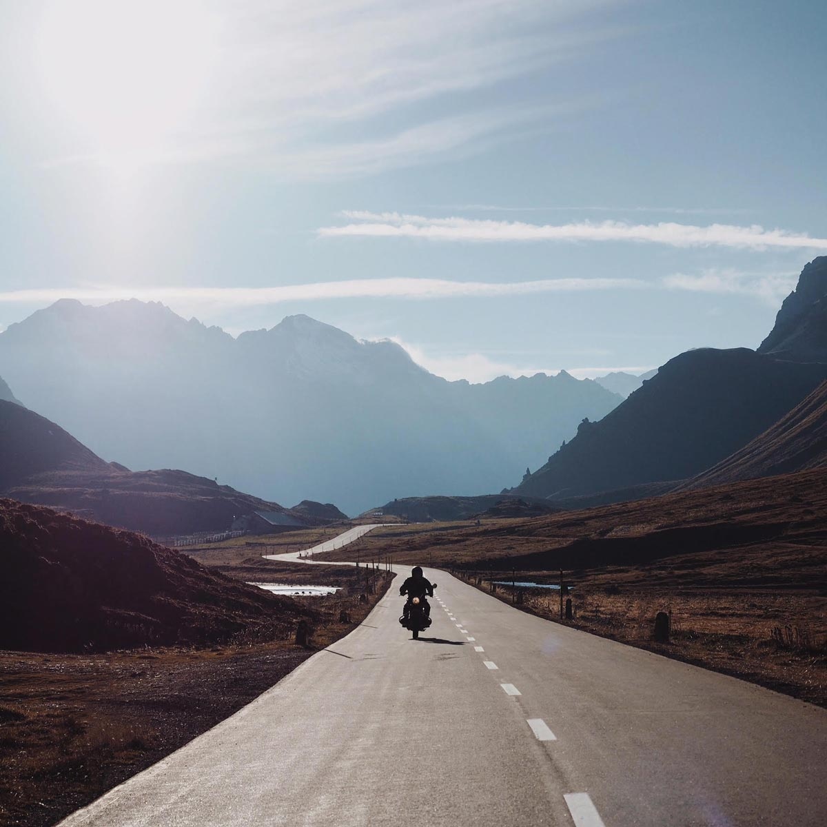 Photo by Martina Bisaz of motorcycle riding down swiss highway with mountainous backdrop
