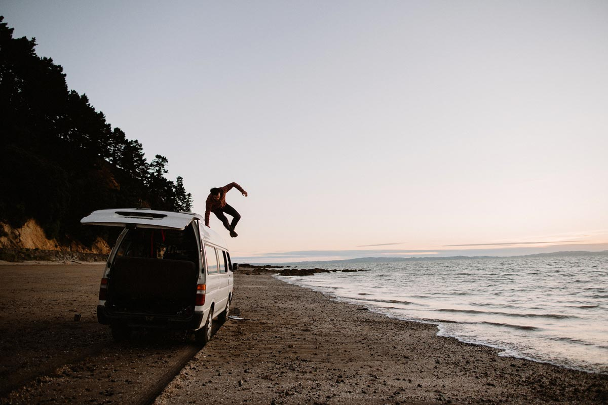Photo by Greg Balkin of man jumping off top of camper parked on the beach