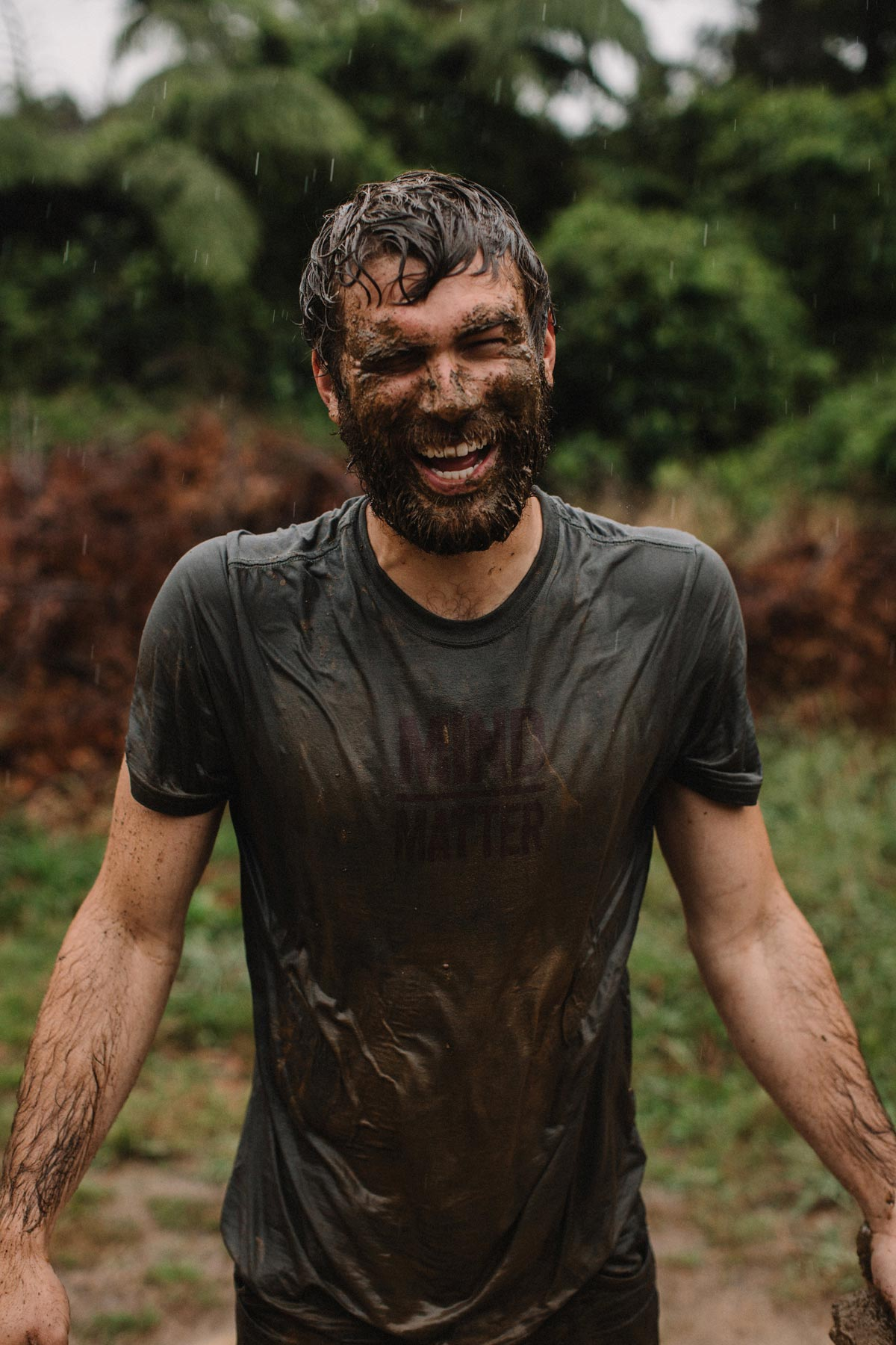 Photo by Greg Balkin of man caked in mud laughing in the rain