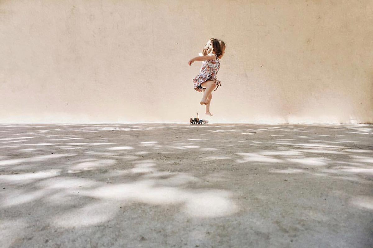 Photo by Jenny Rogers of little girl jumping and playing in speckled sunlight