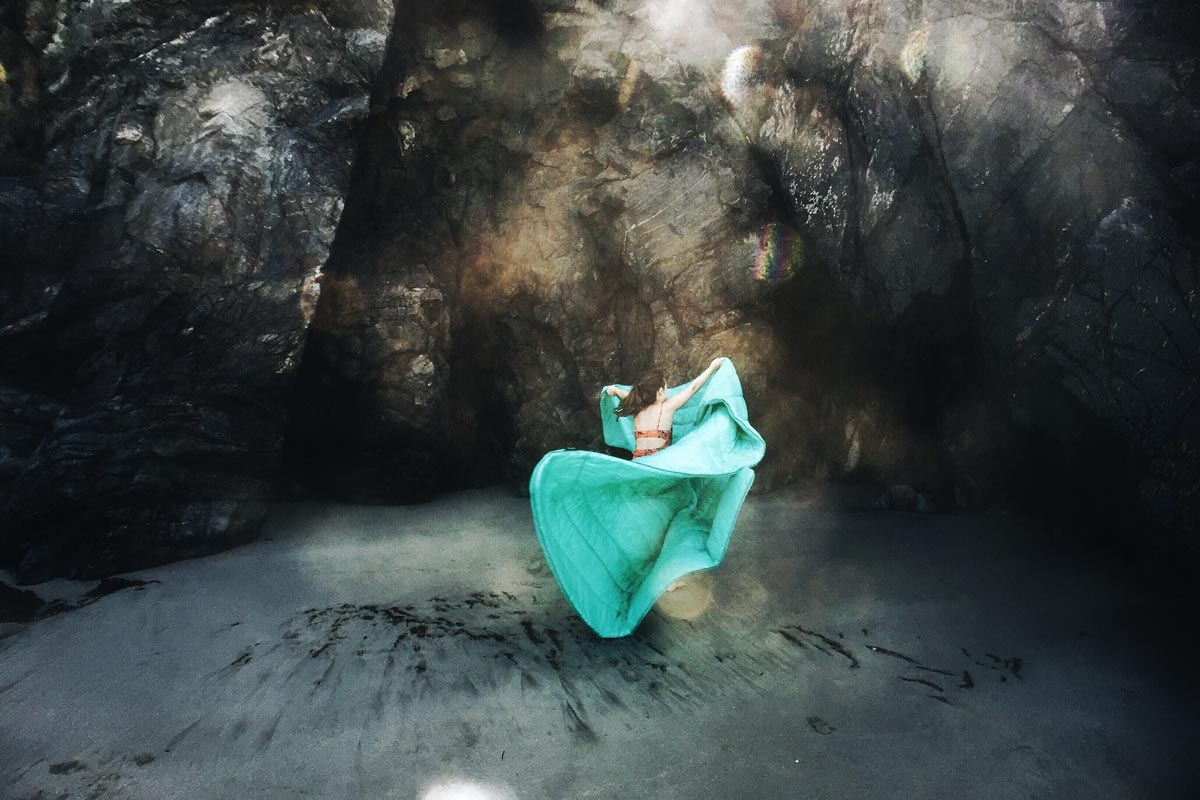 Photo by Jenny Rogers of someone throwing down blanket for seating in Big Sur cave