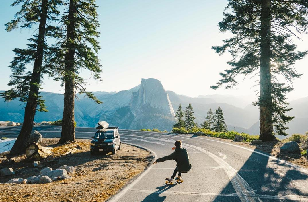 Photo by Joel Bear of man skateboarding in yosemite with halfdome in background
