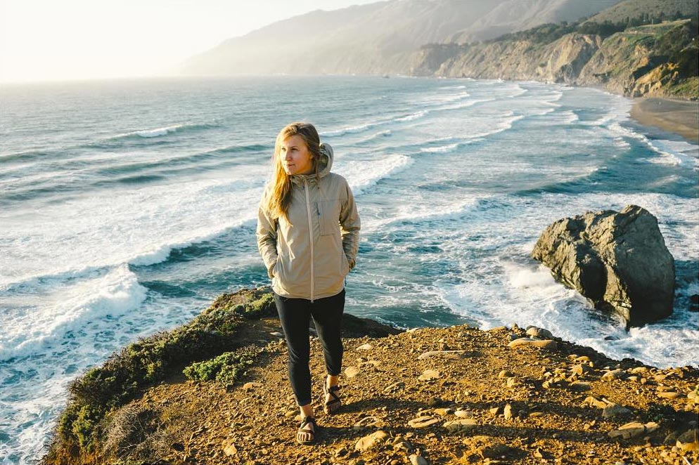 Photo by Joel Bear of woman standing on cliffside with ocean in the background