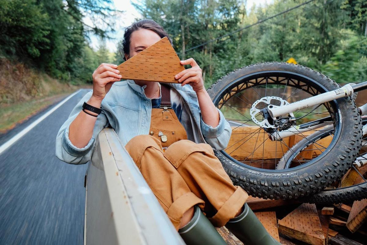 Photo by Jules Davis of smiling woman in the back of a truck next to dirtbike