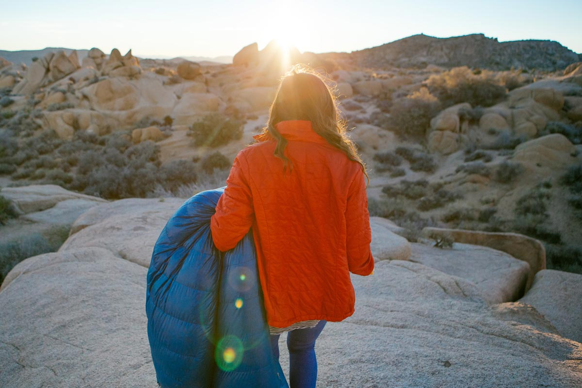 Photo by Jules Davis of woman holding sleeping bag and walking toward Joshua Tree sunrise