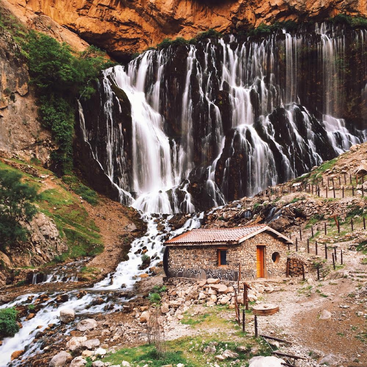 Dan Rubin photo of small hut in front of waterfall