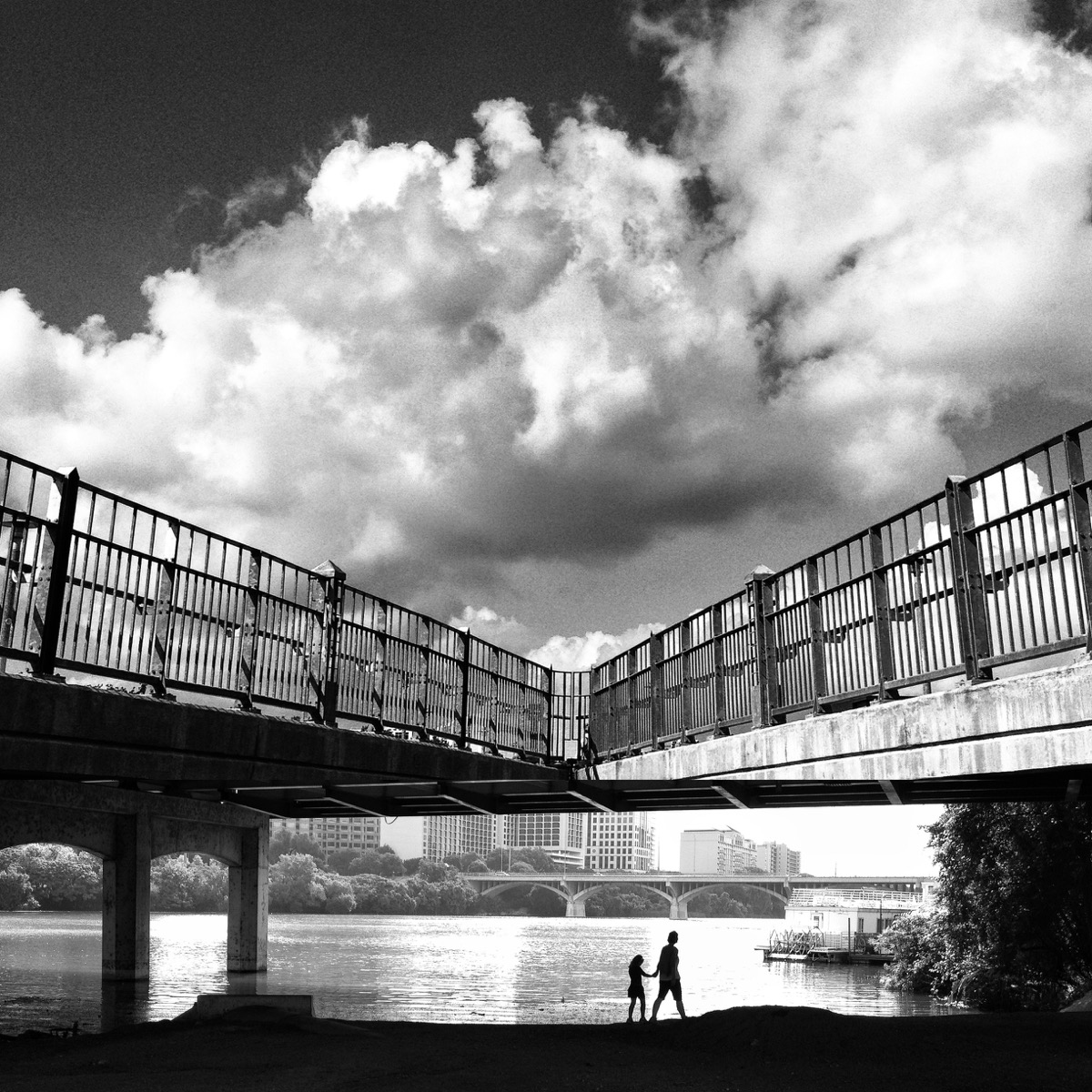 Inkedfingers photo in black and white of parent and child walking on waterfront below bridge