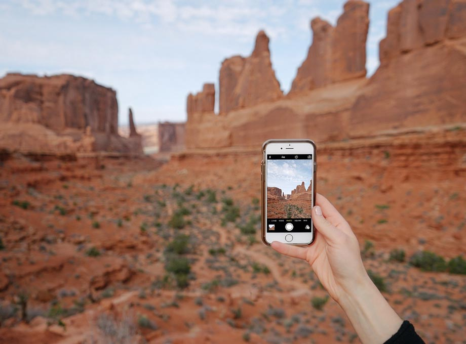 Phone screen taking photo of red rock formations