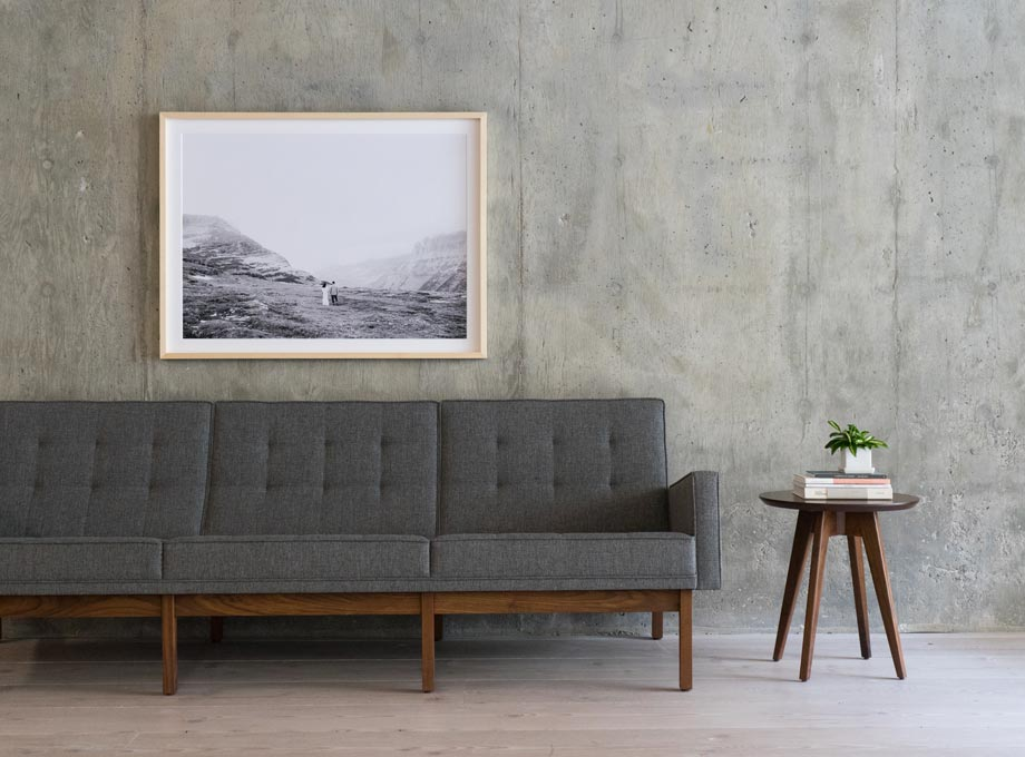 Framed black and white photo hanging above grey couch in modern space