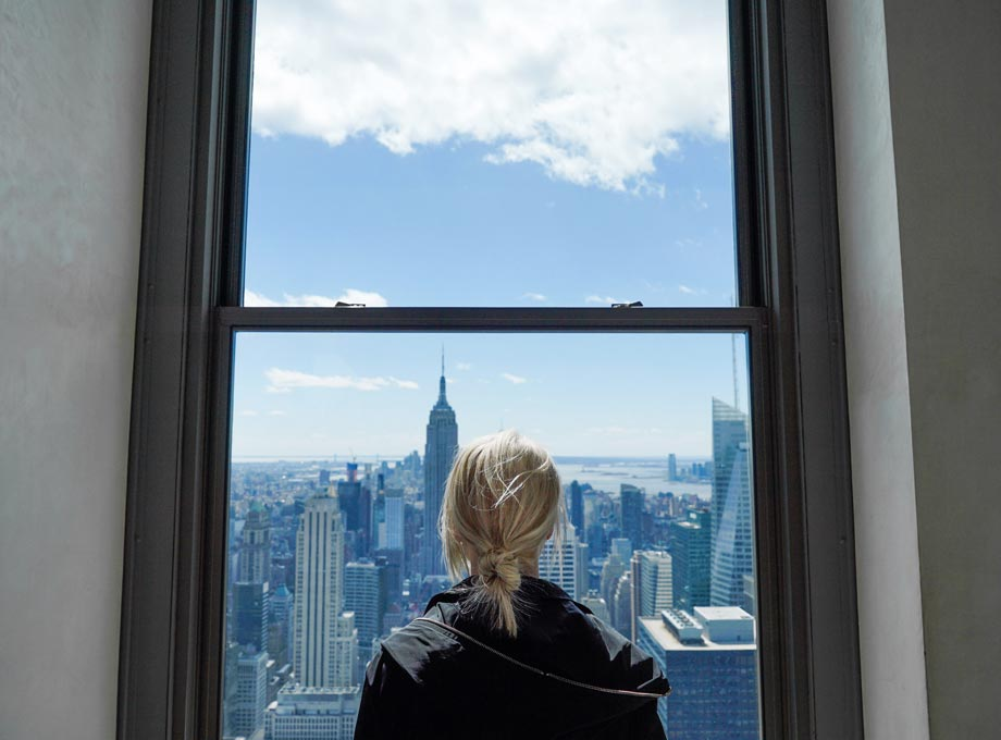 Woman staring out window at city skyline