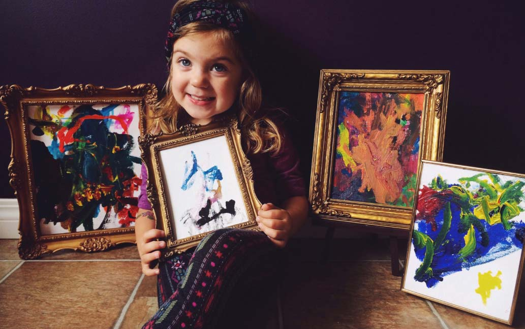 Little girl holding a painting
