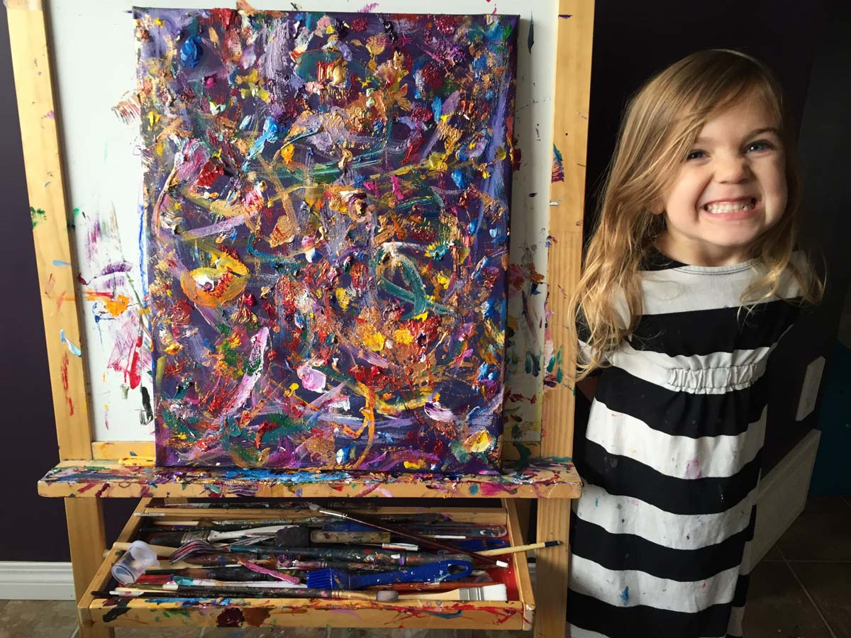 Small girl smiling next to vibrant painting
