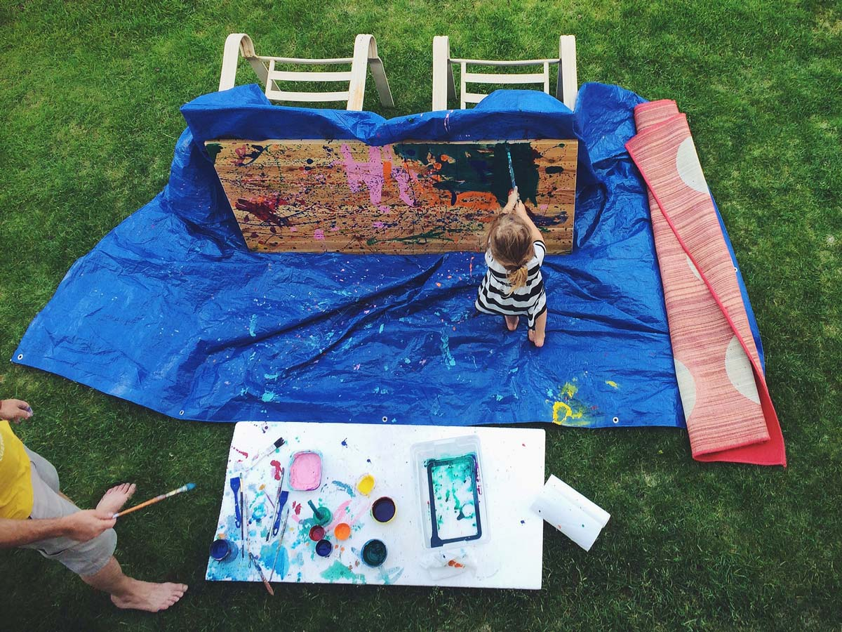 Young girl painting on a tarp laid on the grass