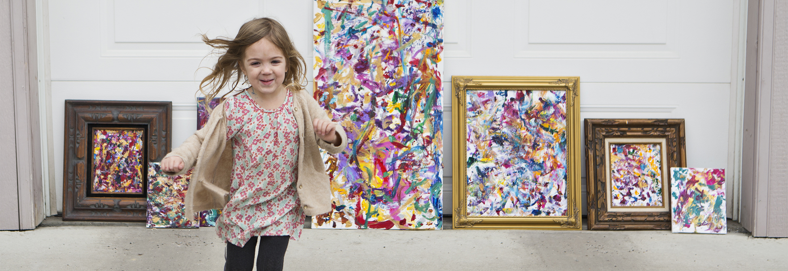 Small girl running away from paintings leaned against a garage.