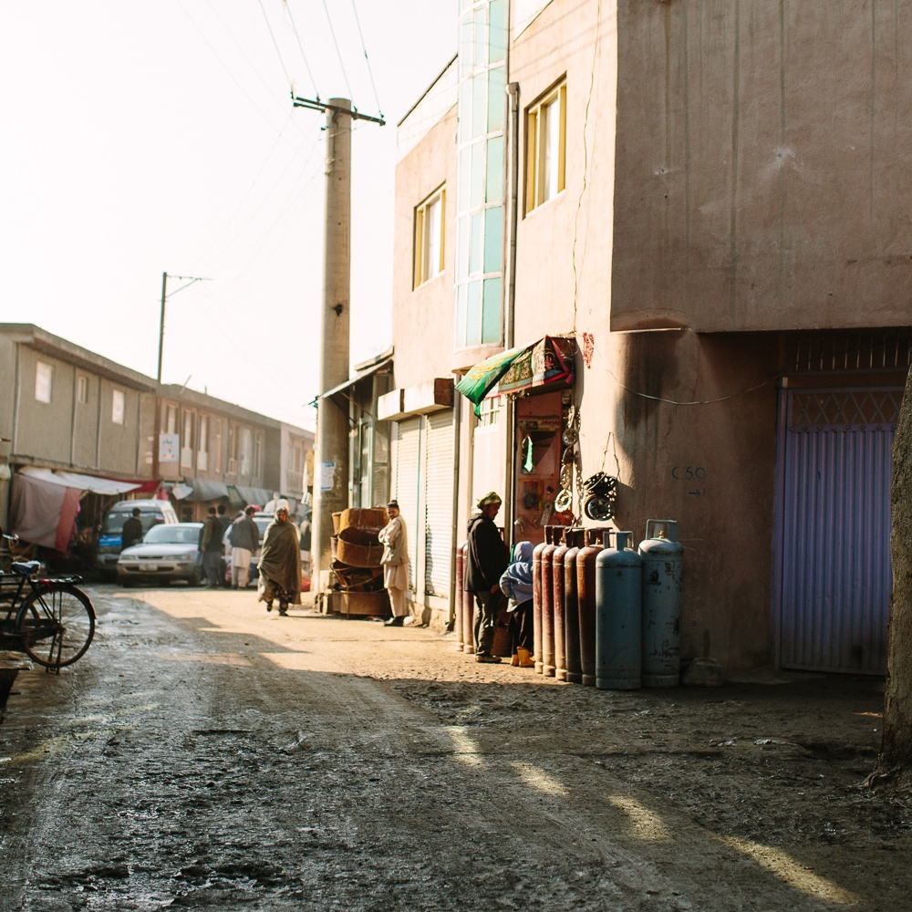 Muddy streets with people clinging towards sides of buildings