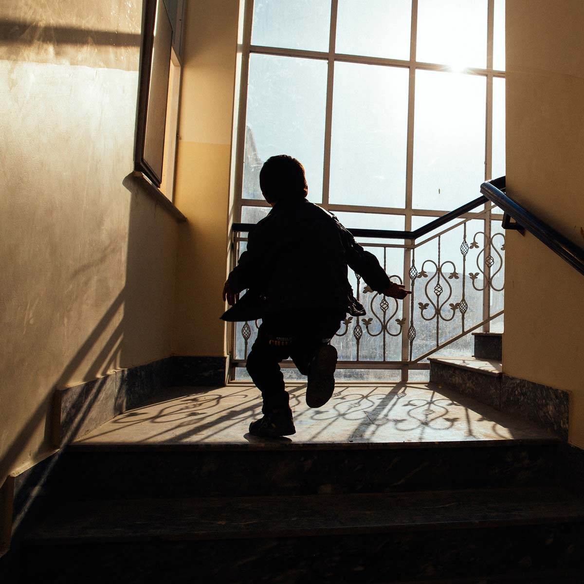 Silhouette of a small child running down the stairs